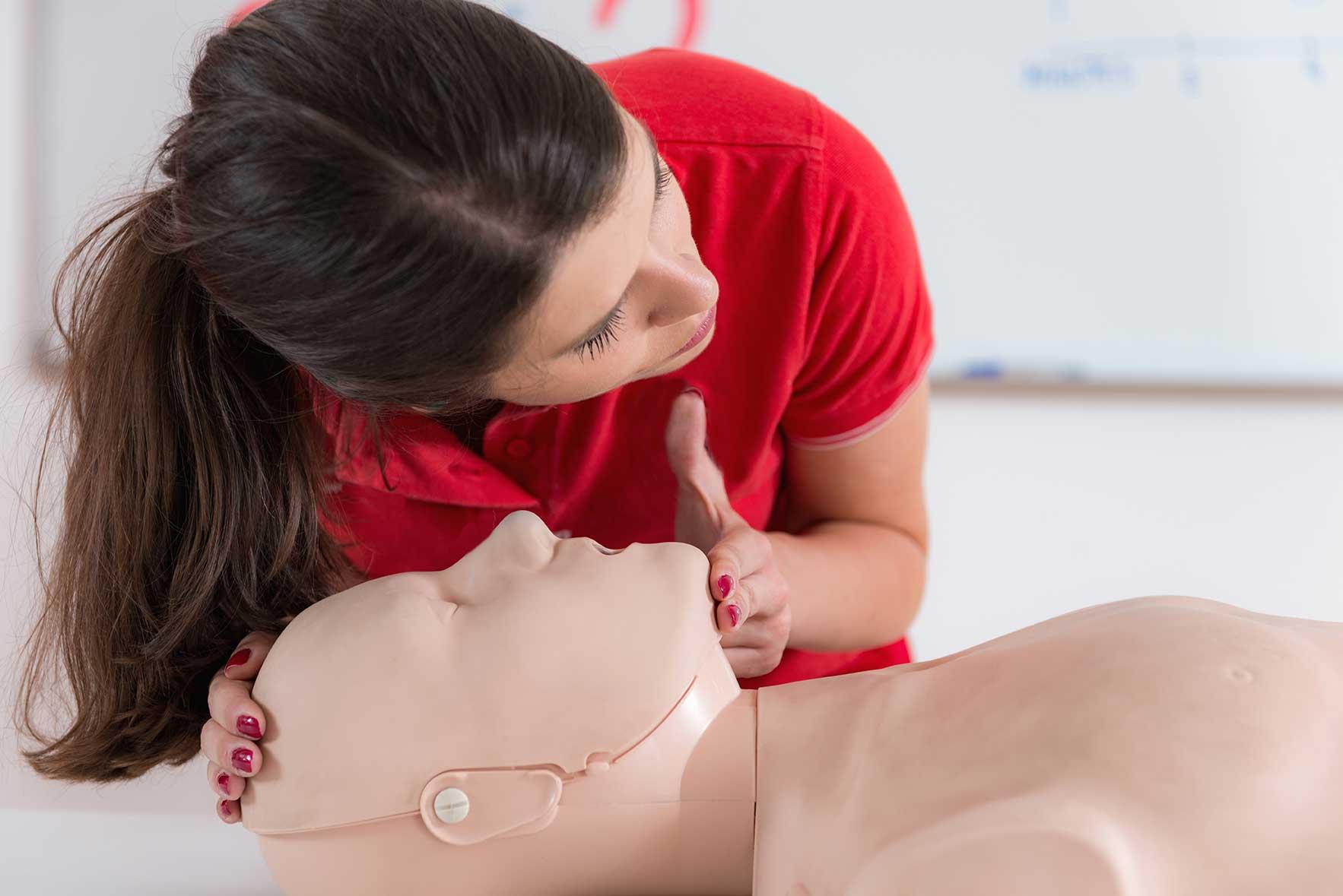 Kvinna som utbildar i HLR på en docka, hjärt-lungräddning, första hjälpen