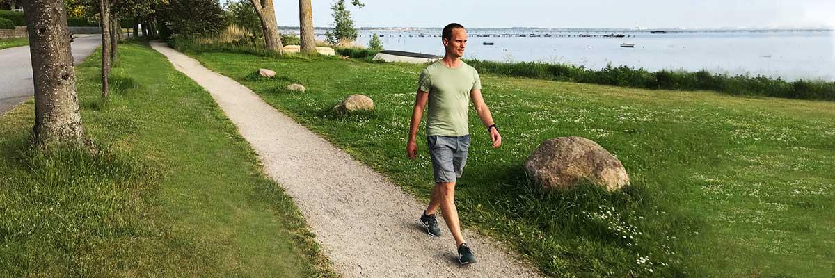 man som promenerar och konditionstränar längs stig vid havet