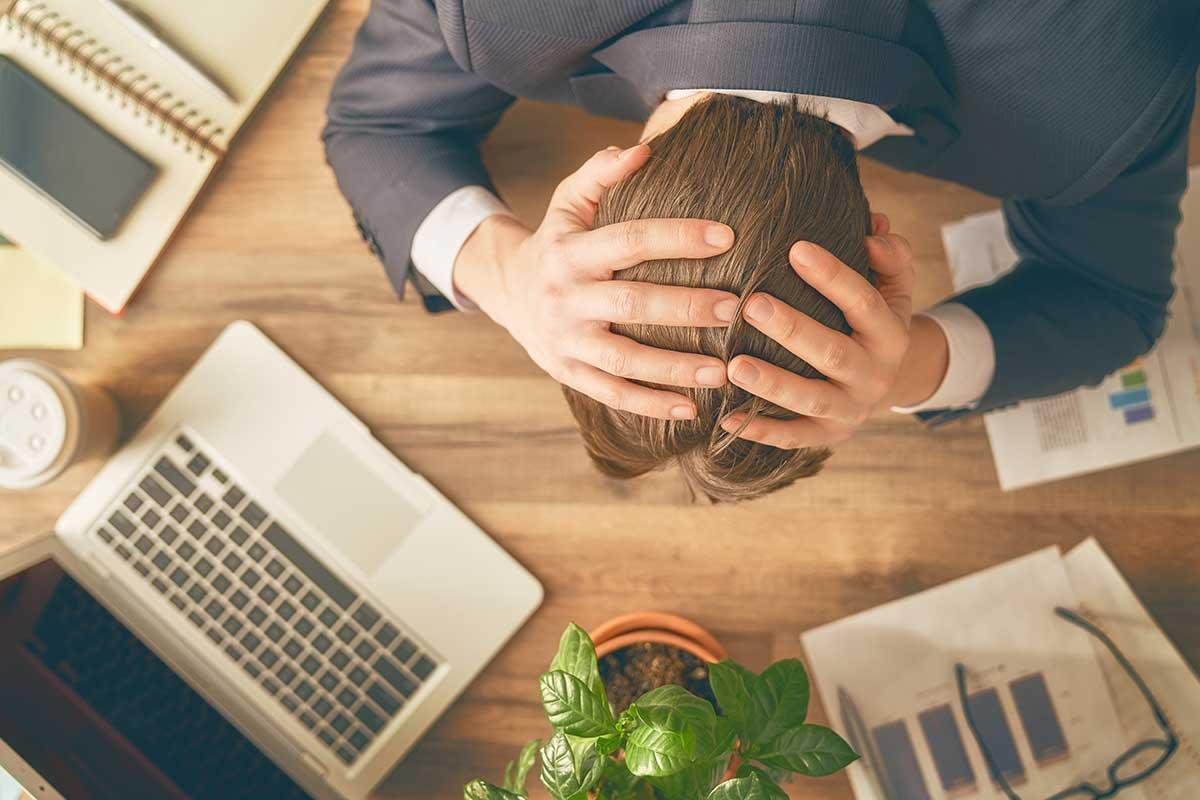 Man som har händerna på huvudet på jobbet och därför ger ett deprimerat stressat intryck